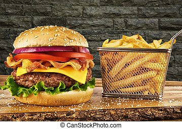 Cheeseburger with bacon and a basket of french fries. Brick wall in background. Copy space for your text.