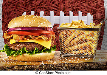Cheeseburger with bacon and a basket of french fries. Football ball image in background.