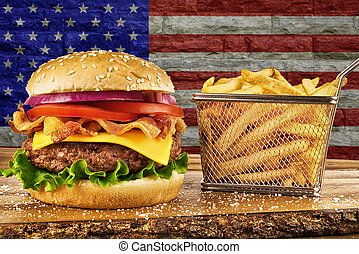 Cheeseburger with bacon and a basket of french fries. USA flag's on brick wall in background.