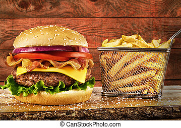 Cheeseburger with bacon and a basket of french fries. Wooden plank in background. Copy space for your text.