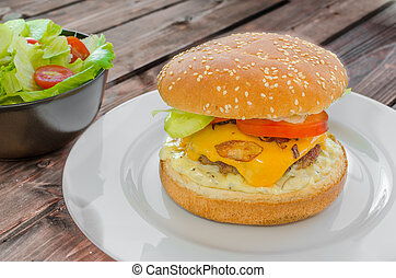 Cheeseburger with bacon and tartar sauce and garden salad