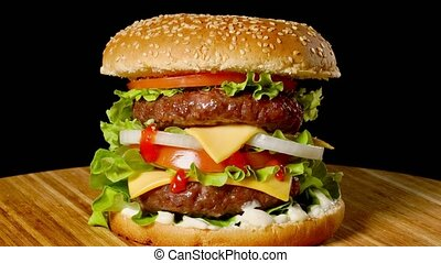 Cheeseburger with bacon on a dark background. Close-up....