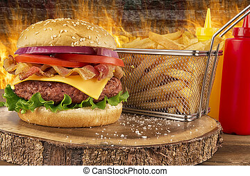 Cheeseburger with beef patty and bacon. French fries in basket, ketchup and mustard bottle. Fire in background.