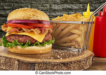Cheeseburger with beef patty and bacon. French fries in basket, ketchup and mustard bottle in background. Isolated on brick wall. Real close up.