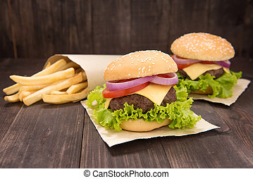 Cheeseburger with french fries on wooden background