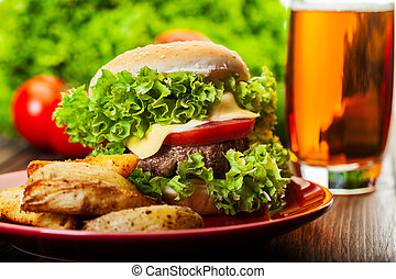 Cheeseburger with fried potatoes on a plate with beer