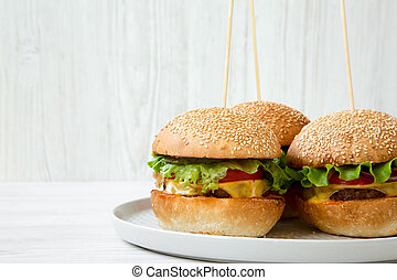 Cheeseburgers on grey plate. White wooden background. Side view. Close-up. Copy space.