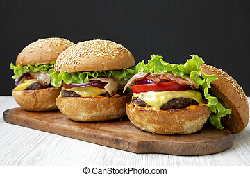 Cheeseburgers on rustic wooden board, side view. Close-up.