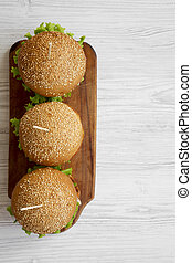 Cheeseburgers on wooden board over white wooden background, overhead view. Copy space.