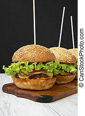 Cheeseburgers on wooden board, side view. Close-up.