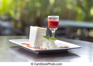 cheesecake with cherry on wooden table.