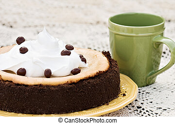 Cheesecake garnished with chocolate covered coffee bean with shallow DOF.