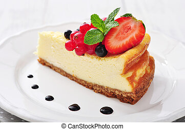 Cheesecake with fresh berries and mint on plate closeup