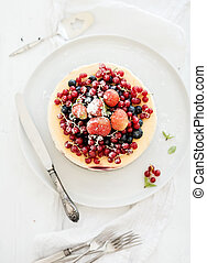 Cheesecake with fresh garden berries on top over white wooden table surface. Selective focus