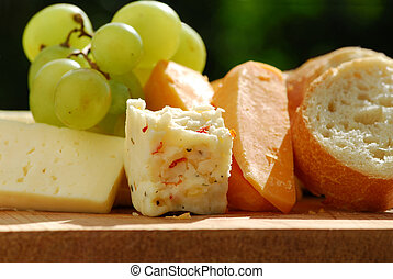 Cheeses - Assorted cheeses with grapes and white bread