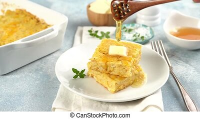Slices of cheesy cornbread freshly baked served with butter and honey, southern food with honey poured over