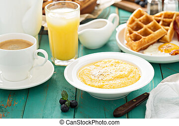 Cheesy grits with butter in a white bowl for breakfast
