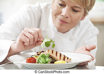 Chef Adding Garnish To Meal In Restaurant Kitchen