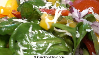 Chef adding parmesan cheese to a spinach salad with bell...