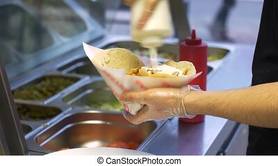 chef adding sauce to pita with meat at kebab shop - fast...