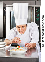 Chef Adding Spices To Dish