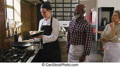 Front view of a multi-ethnic group of senior adults at a cookery class in a restaurant kitchen, the diverse group of adult students listening to instructions from a Caucasian female chef wearing chefs whites and a black hat and apron, putting fresh vegetables into a hot wok to stir fry, in slow ...