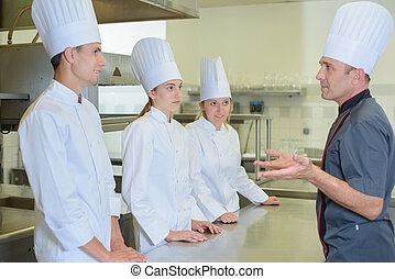 Chef addressing trainee cooks