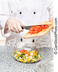 chef adds chopped tomatoes in a glass bowl
