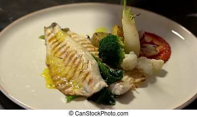 Chef adds sauce on fish fillet served with vegetables. Grilled fish steak with steamed vegetables on white plate. Healthy food concept.