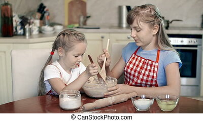 Chef and Assistant - Little girl adding ingredients to the...