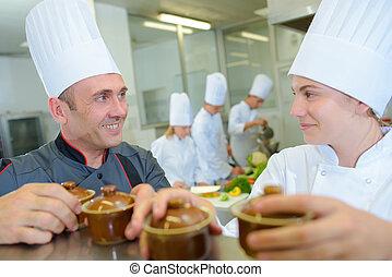 Chef and trainee holding ramekin pots