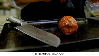 Chef applying oil on bacon in kitchen 4k