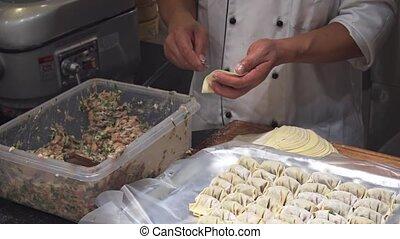 Chef Assembling Dumplings in a Singapore Restaurant - Local...