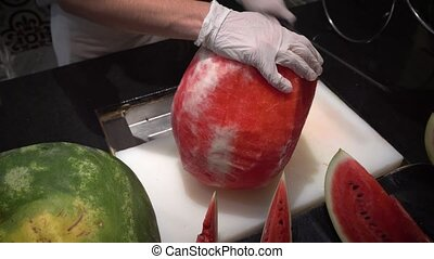 chef at restaurant cuts a big red watermelon with a large...