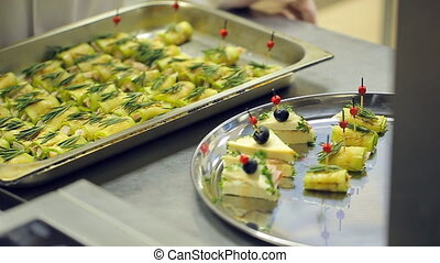 Chef catering services, disposable gloves, lays roasted snacks from baking sheet on a tray.