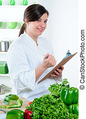 Chef Checking Menu - Female Chef In Her Kitchen Checking The...