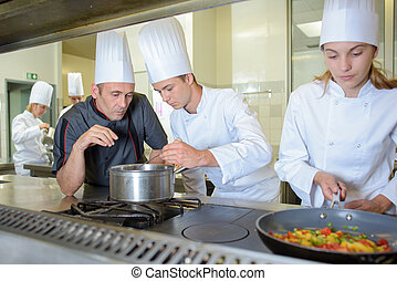 Chef checking work of trainee cooks
