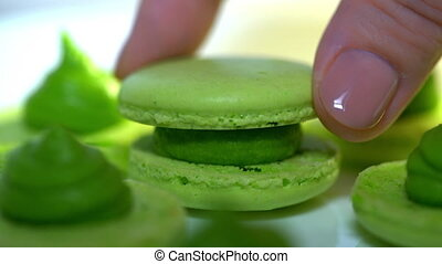 Chef connecting two halves of green pistachio macaroons with...