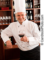 Chef cook hold wine glass in restaurant