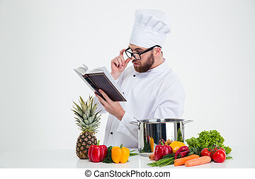 Chef cook in glasses reading recipe book