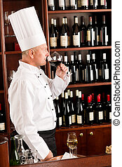 Chef cook smell wine glass in restaurant