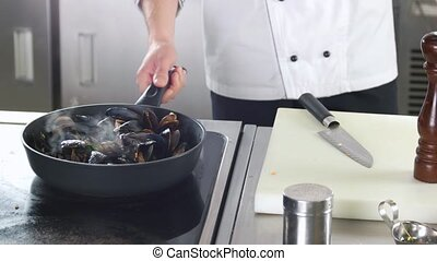 Chef cooking mussels, frying pan. Shellfish and chopped...