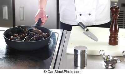 Chef cooking mussels.