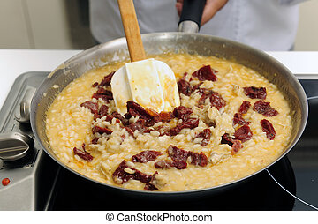 Chef cooking risotto with dried tomato stirring