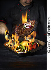 Chef cooking steak and vegetables in pan with fire flame on dark background. Restaurant and hotel service concept.