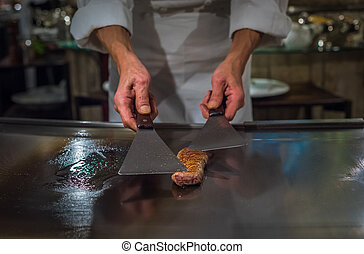 Chef cooking wagyu beef in Japanese teppanyaki restaurant, ...