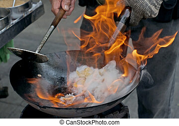 chef cooking with fire in frying pan at outdoor kitchen