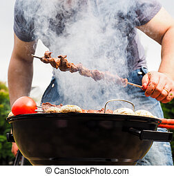 Chef covered in smoke grilling skewers