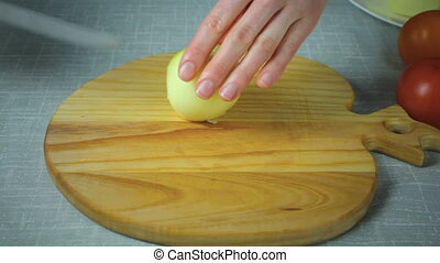Chef cuts a piece of yellow onion on a wooden board - Girl...