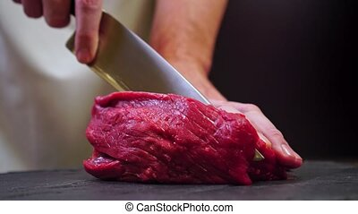 Chef cuts beef for steak.